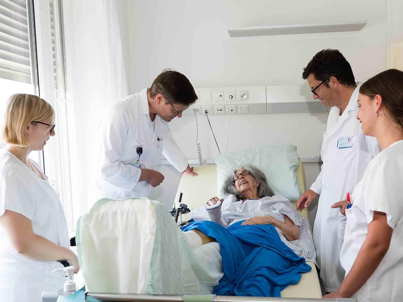 Alterstraumatologie ist Teamarbeit: Geriater Dr. Sacha Beck (2.v.l.) und Unfallchirurg Dr. Michael Dietrich zusammen mit Physiotherapeutin Rahel Arnold und Pflegefachfrau Sanja Moravac am Bett von Patientin Lisette Miéville.