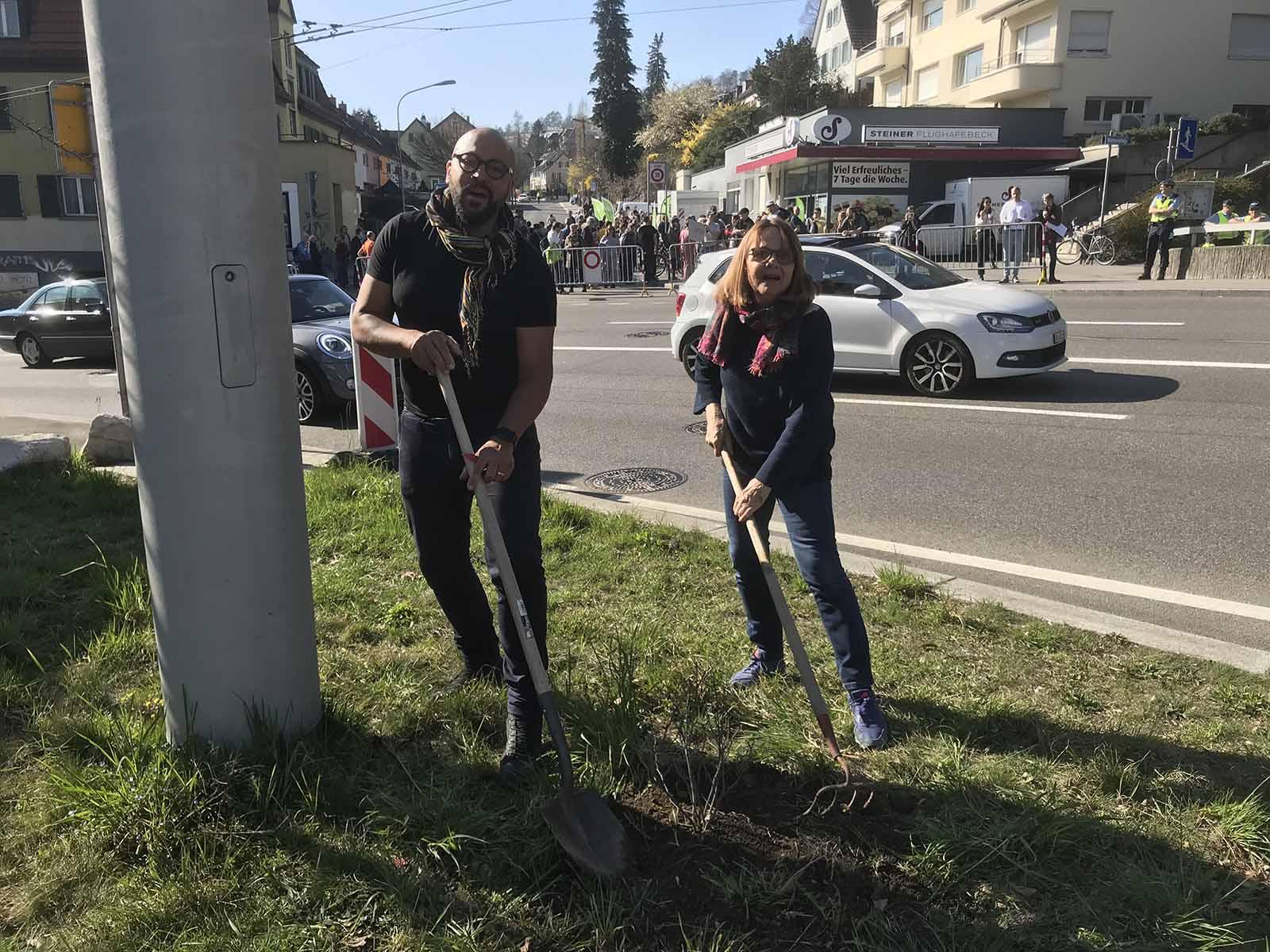 Eva Gut und Andrew Katumba pflanzten an der Rosengarten-Demo einen Rosenbusch. Ironischer Weise taten die damit vielleicht mehr für die Feinstaubreduktion als der Kanton mit seinem Milliardentunnel.