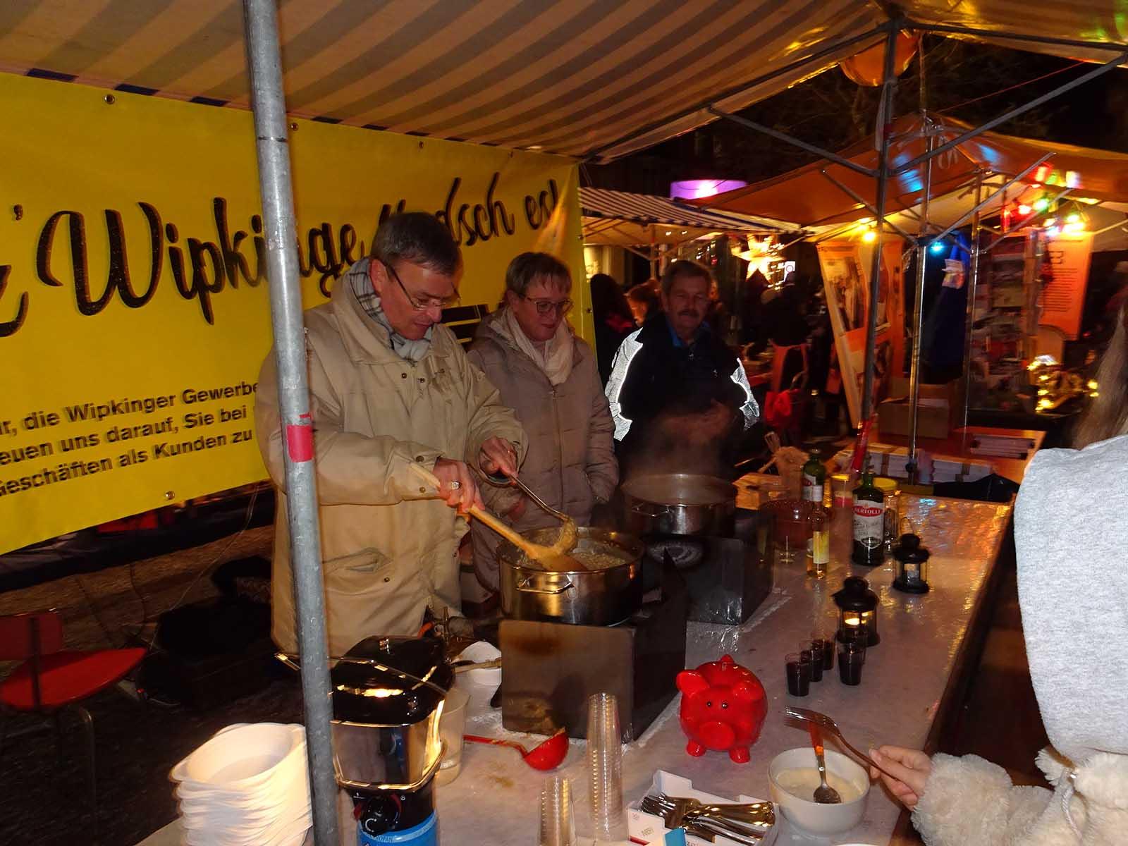 Vorstandsmitglieder des Gewerbe Wipkingen bereiten am Weihnachtsmarkt den traditionellen Risotto zu.