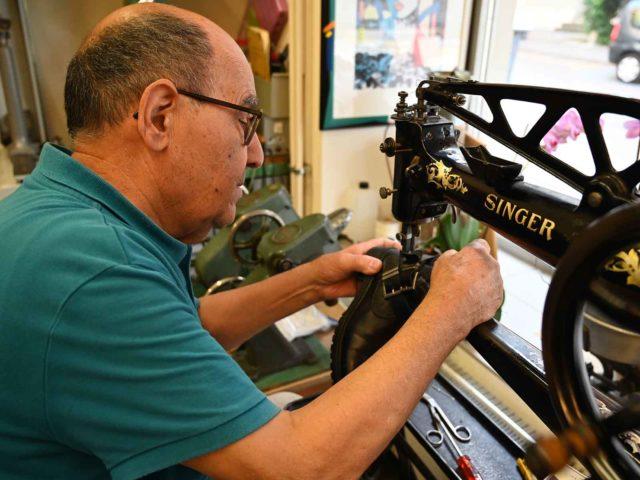 Schuhmacher Antonio Stefano an seiner Singer Nähmaschine. Er hofft, seine alte Kundschaft bald wiederzusehen.