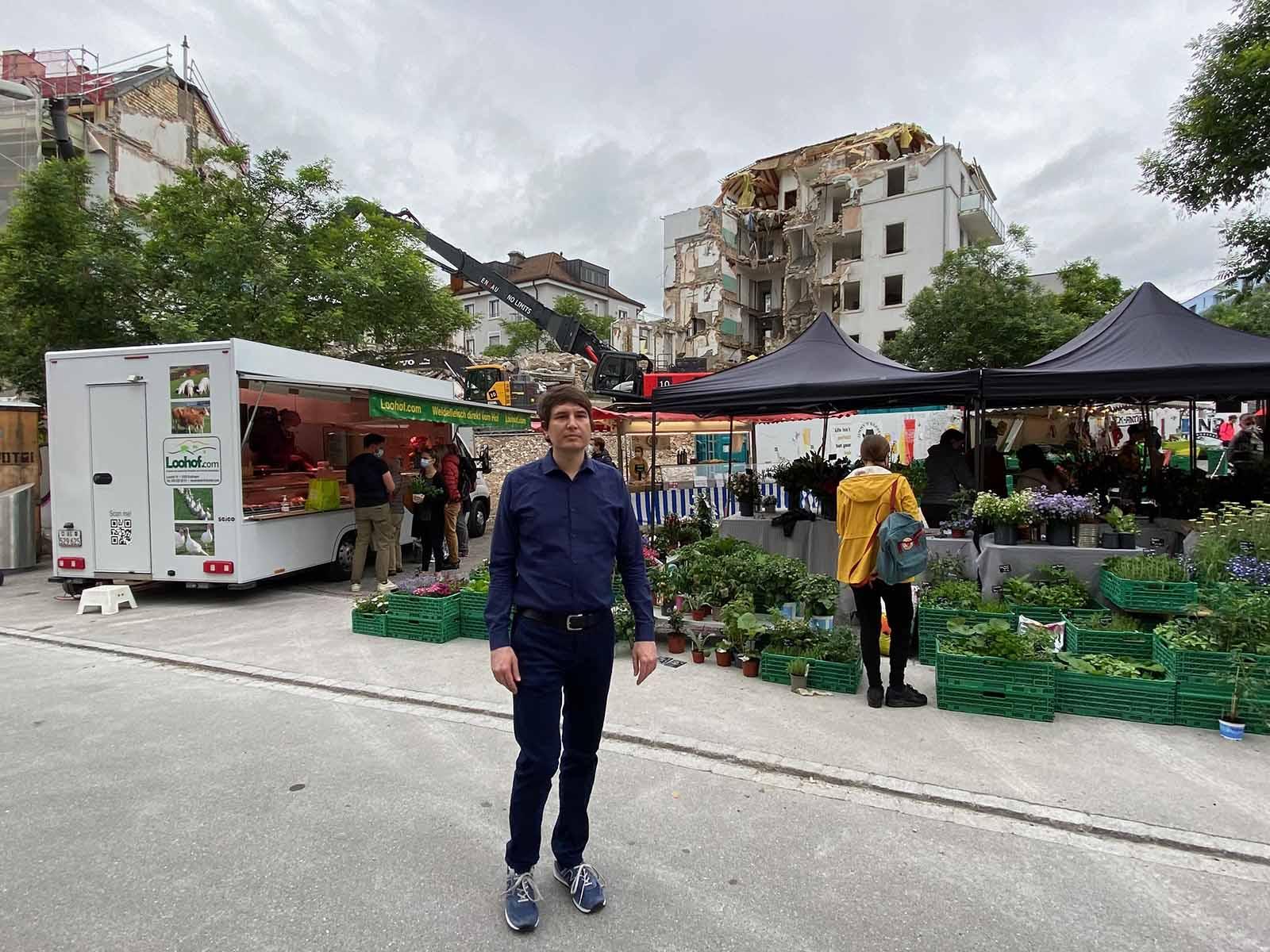 Florian Utz vor dem Wochenmarkt und der dramatischen Abbruch-Szenerie am Röschibachplatz im Hintergrund. Ein Schaubild der Gentrifizierung.