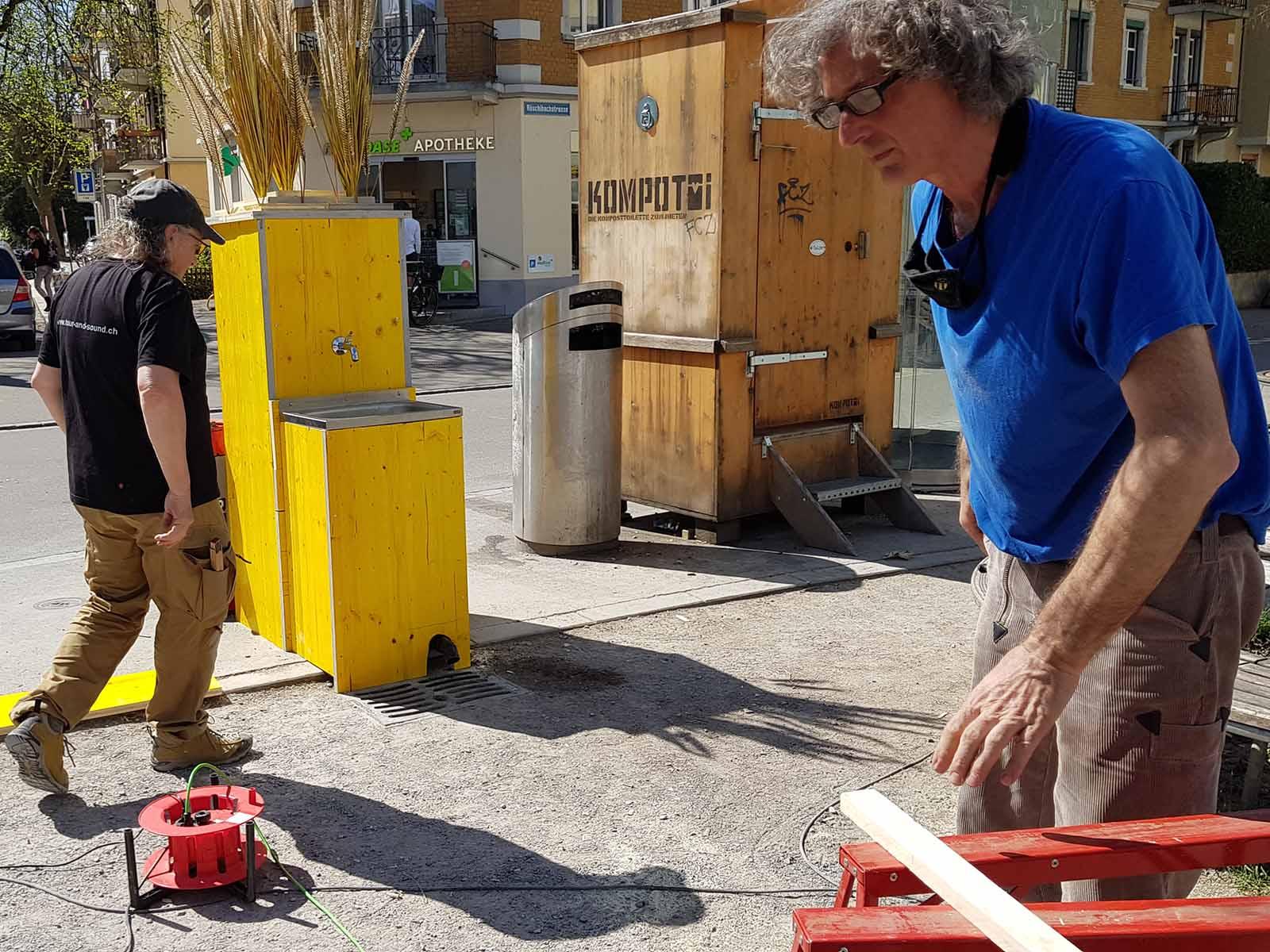 Peter Keller (rechts) mit seinem Helfer Luis beim Bau des Brunnens auf dem Röschibachplatz.
